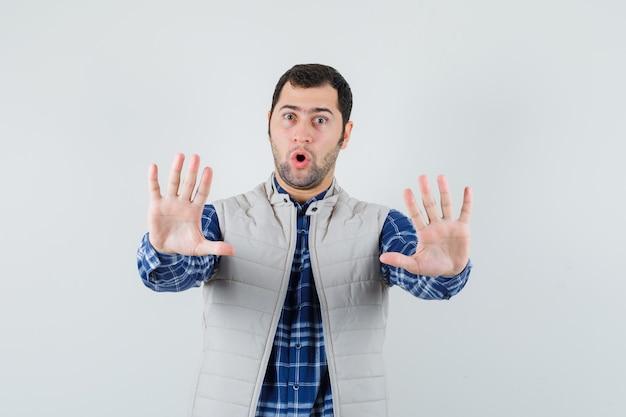 シャツ、ノースリーブのジャケットで停止ジェスチャーを示し、問題を抱えているように見える若い男性。正面図。