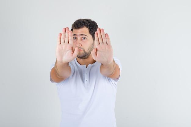 Молодой мужчина показывает жест стоп в белой футболке и выглядит с отвращением