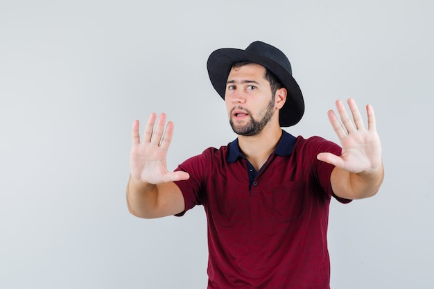 Young male showing stop gesture in t-shirt,hat and looking excited. front view.