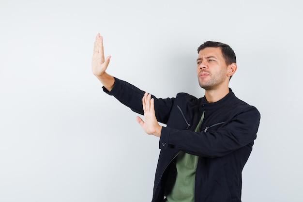 Giovane maschio che mostra il gesto di arresto in maglietta, giacca e sembra annoiato. vista frontale.