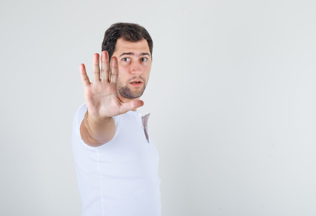 Giovane maschio che mostra il gesto di arresto in maglietta bianca e che sembra disgustato