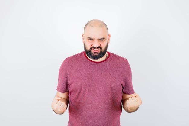 Giovane maschio che mostra gesto di successo in maglietta rosa e sembra potente, vista frontale.