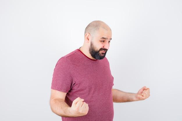 Giovane maschio che mostra gesto di successo in maglietta rosa e sembra potente. .