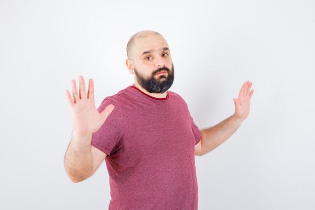 Giovane maschio che mostra gesto di resa in maglietta rosa e sembra ansioso.