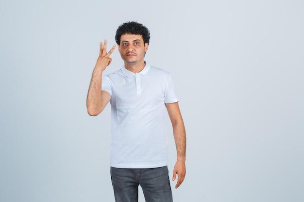 Молодой мужчина показывает три пальца в белой футболке, брюках и выглядит уверенно, вид спереди.