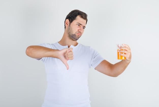 Молодой мужчина показывает палец вниз с соком в белой футболке и выглядит недовольным.