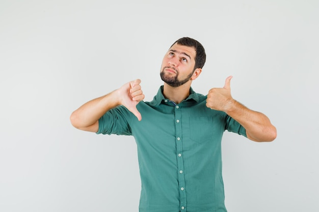Молодой мужчина показывает большой палец вверх и вниз одновременно в зеленой рубашке и выглядит смущенным. передний план.