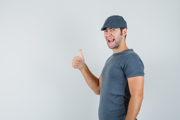 Young male showing thumb up in grey t-shirt cap and looking happy