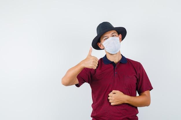 빨간 셔츠, 흰색 마스크를 쓴 젊은 남성이 엄지손가락을 치켜들고 만족스러워 보입니다. 텍스트를 위한 공간