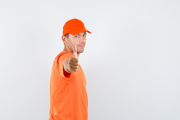 Young male showing thumb up in orange t-shirt and cap and looking pleased