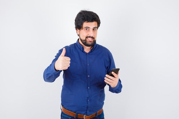 로얄 블루 셔츠에 전화를 들고 기뻐하는 동안 엄지 손가락을 보여주는 젊은 남성. 전면보기.