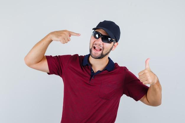 Молодой мужчина показывает палец вверх, указывая на свои очки в футболке, черных очках и выглядит довольным, вид спереди.