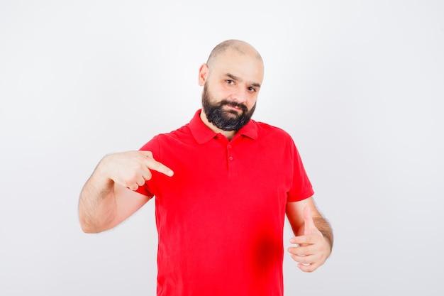Молодой мужчина показывает палец вверх, указывая на него в красной рубашке и выглядит уверенно. передний план.