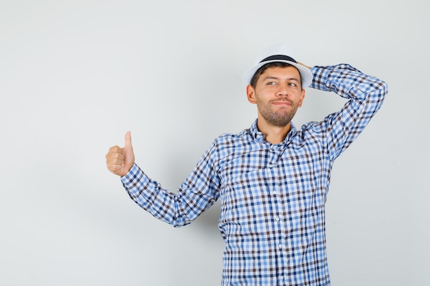 チェックシャツを着て帽子に親指を上げて満足そうに見える若い男性