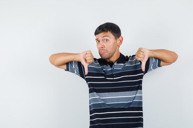 Молодой мужчина показывает палец вниз в футболке и выглядит разочарованным, вид спереди.