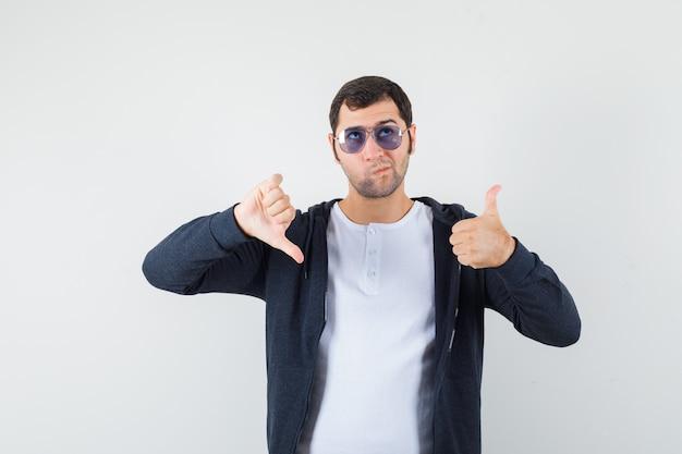 Tシャツ、ジャケットで親指を上下に見せ、躊躇している若い男性。正面図。