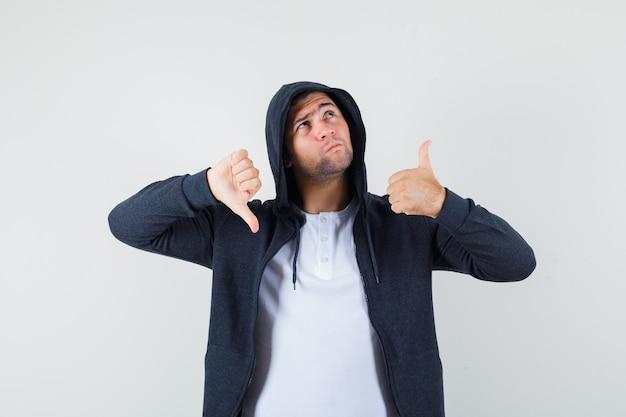 Tシャツ、ジャケットで親指を上下に見せて、毅然とした表情をしている若い男性。正面図。