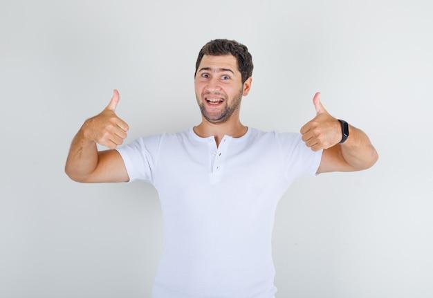 若い男性が白いtシャツに親指を表示して幸せそうに見えて