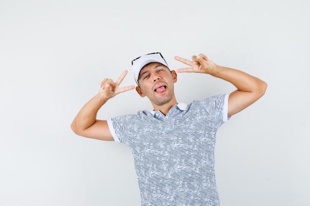 Tシャツとキャップでvサインを示し、狂ったように見える若い男性