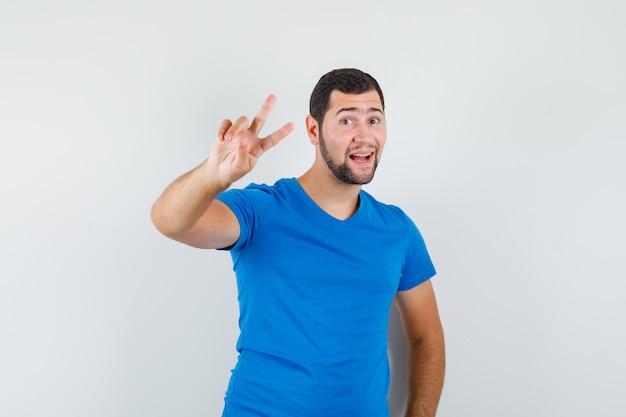 青いtシャツで勝利のサインを示し、うれしそうに見える若い男性