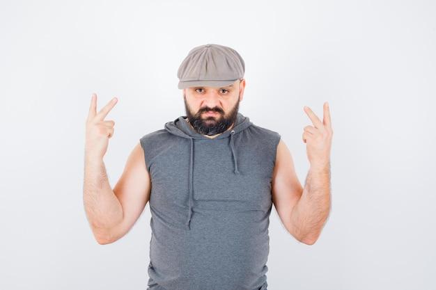 Молодой мужчина показывает знак победы в безрукавке с капюшоном, кепке и выглядит удачливым, вид спереди.