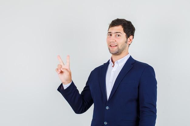 スーツに勝利のサインを示し、うれしそうに見える若い男性。正面図。