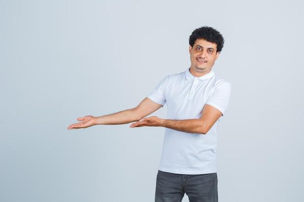 흰색 티셔츠, 바지를 입고 자신감을 갖고 환영하는 제스처를 보이는 젊은 남성. 전면보기.