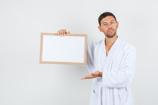 Young male showing white board in white bathrobe and looking strict. front view.