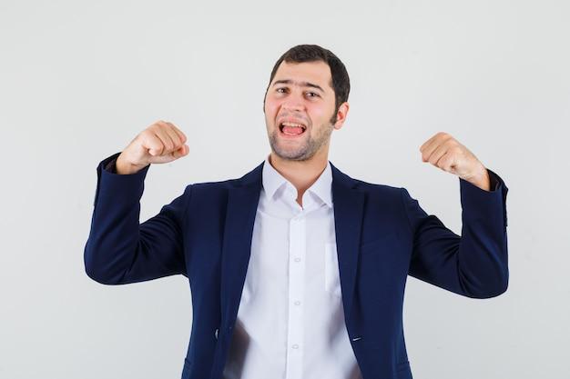 Молодой мужчина показывает жест победителя в рубашке и куртке и выглядит счастливым