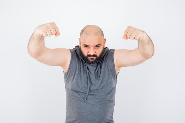 Молодой мужчина показывает жест победителя в толстовке без рукавов и выглядит удачливым. передний план.