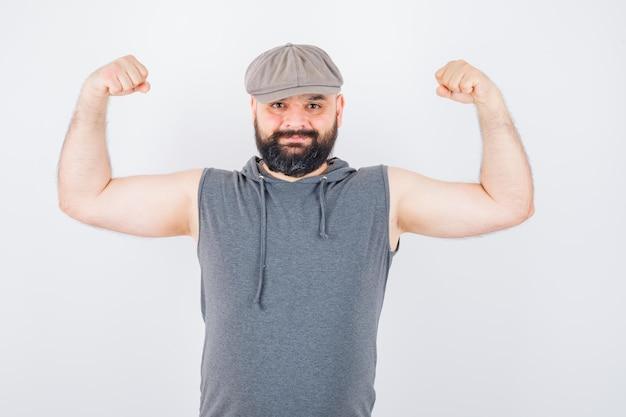 Молодой мужчина показывает жест победителя в балахоне без рукавов, кепке и выглядит удачливым, вид спереди.