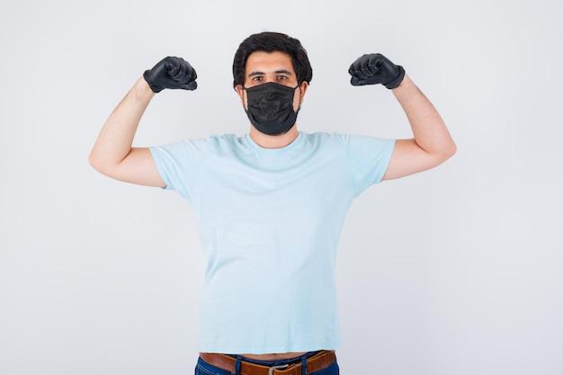 Молодой мужчина показывает жест победителя в футболке и выглядит удачливым, вид спереди.