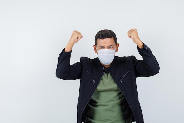 Молодой мужчина показывает жест победителя в футболке, куртке, маске и выглядит решительным, вид спереди.