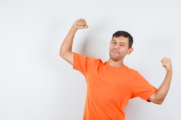 Young male showing winner gesture in orange t-shirt and looking happy