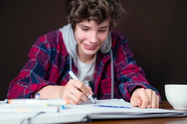 테이블에 앉아 마커 b가 있는 노트북에 그림을 그리는 젊은 남성