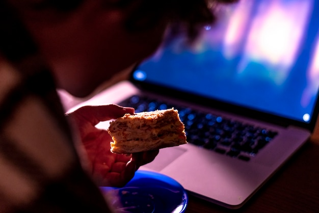 Young male sitting in front of laptop watch movies and eat sweet cake in the night at home f