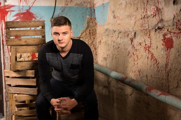 할로윈 공포 컨셉의 끔찍한 지하실에 있는 빈 포장 상자에 앉아 있는 젊은 남성