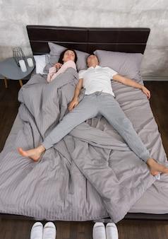 妻と一緒に自由落下姿勢で寝ている若い男性は、キャンドルのあるベッドサイドテーブルの近くで、パジャマを着てベッド全体を占めていました。
