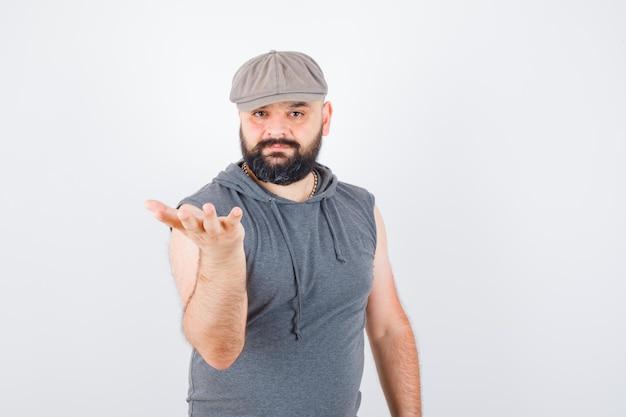 Giovane maschio in felpa con cappuccio senza maniche, berretto alzando la mano in posa interrogativa e guardando fiducioso, vista frontale.