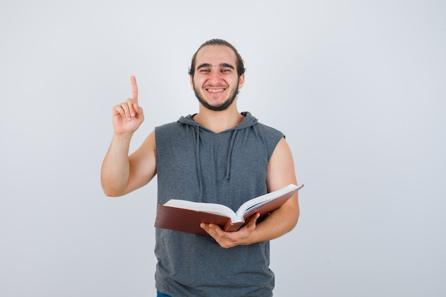 Young male in sleeveless hoodie holding book while pointing up and looking happy , front view.