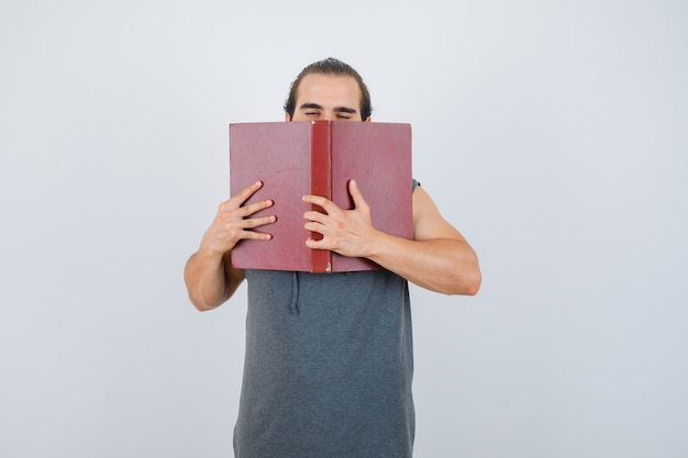 Young male in sleeveless hoodie holding opened book on face and looking sleepy , front view.