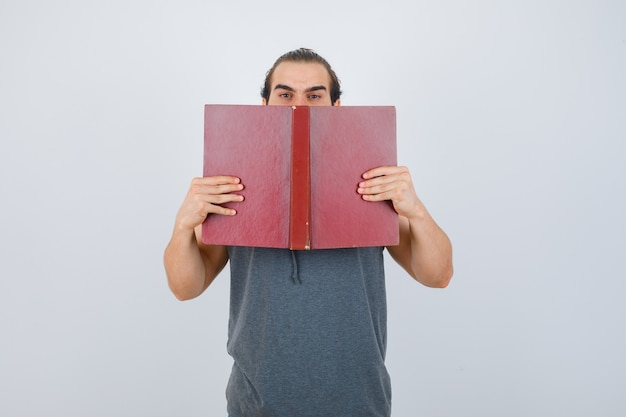 Young male in sleeveless hoodie holding opened book on mouth and looking serious , front view.