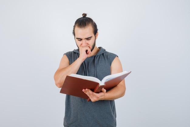 Young male in sleeveless hoodie looking at book while holding hand on mouth and looking thoughtful , front view.