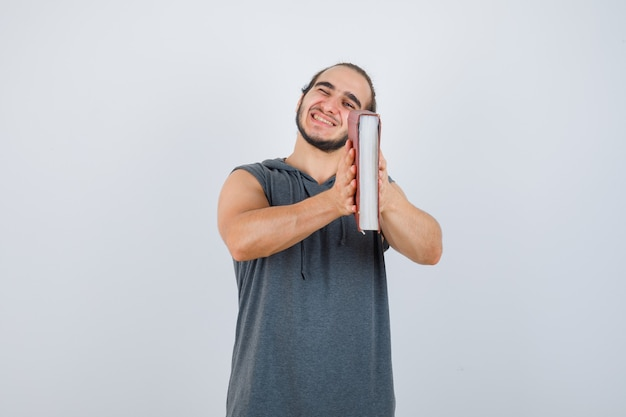 Young male in sleeveless hoodie pretending to peek through a hole with book and looking cheery , front view.