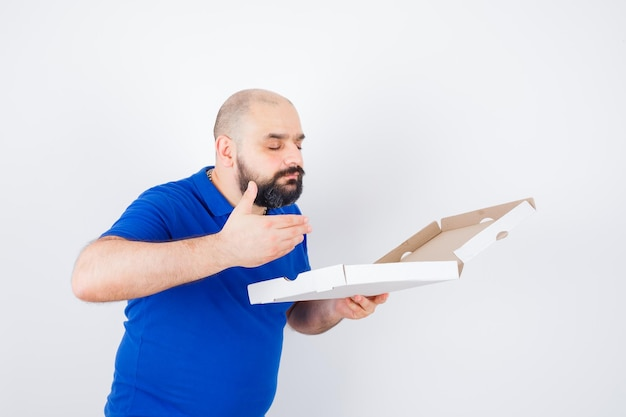 젊은 남성은 티셔츠를 입은 피자 상자를 열고 기뻐하며 정면을 바라보고 있습니다.