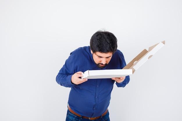 Giovane maschio che odora di aprire la scatola della pizza in camicia, jeans e sembra carino. vista frontale.