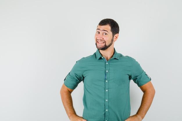 緑のシャツに笑みを浮かべて、かわいく見える若い男性。正面図。