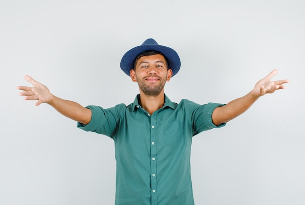 シャツの抱擁のために両手を広げて笑っている若い男性