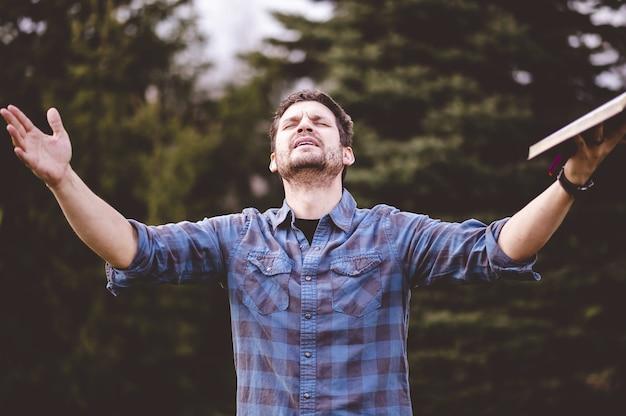 젊은 남성 말하기와 그의 손에 성경을 들고