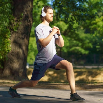 Молодой мужчина-спортсмен в наушниках делает выпады спортивных упражнений на открытом воздухе